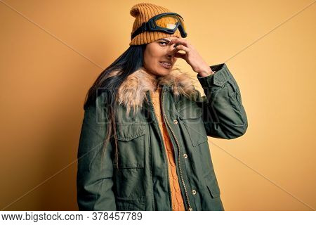 Young beautiful hispanic woman wearing ski glasses and coat for winter weather smelling something stinky and disgusting, intolerable smell, holding breath with fingers on nose. Bad smell