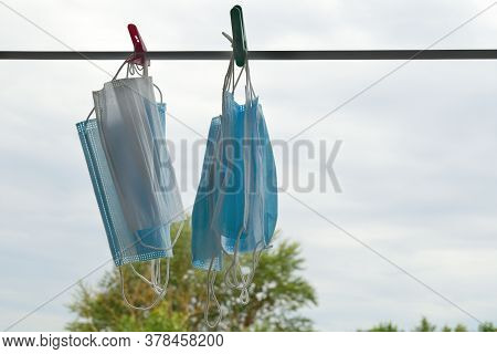 Medical Protective Masks Dry On A Clothesline Against A Blue Sky With Clouds.