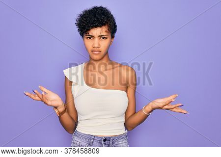 Young beautiful african american afro woman wearing casual t-shirt over purple background clueless and confused with open arms, no idea concept.