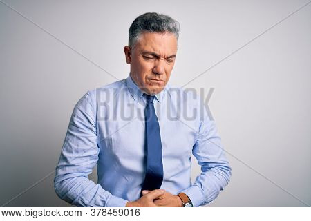 Middle age handsome grey-haired business man wearing elegant shirt and tie with hand on stomach because indigestion, painful illness feeling unwell. Ache concept.