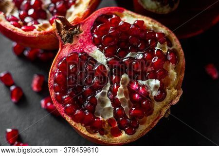 Fresh Pomegranate Fruit And Seeds Close-up On A Black Background