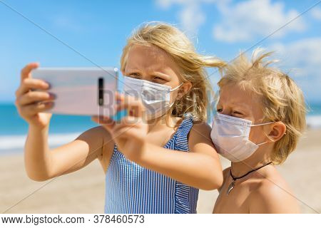 Funny Kids Taking Selfie Photo By Smartphone On Tropical Sea Beach. New Rules To Wear Cloth Face Cov