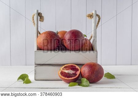 Wooden Crate With Blood Oranges On White Table. Organic Citrus Fruits