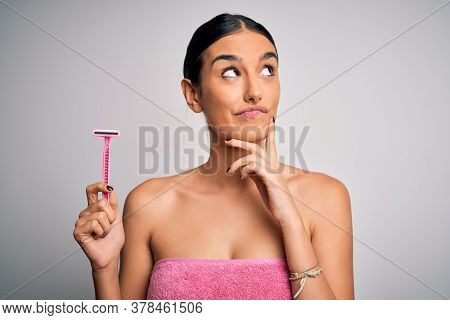 Young beautiful brunette woman wearing towel using razor for depilation serious face thinking about question, very confused idea
