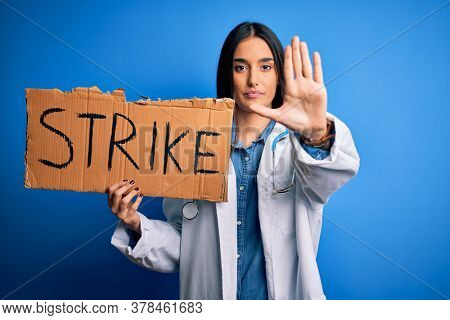 Young doctor woman wearing stethoscope holding cardboard banner protesting in strike with open hand doing stop sign with serious and confident expression, defense gesture
