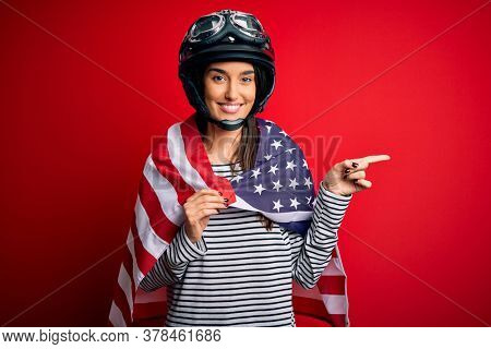 Young beautiful patriotic motorcyclist woman wearing moto helmet and united states flag very happy pointing with hand and finger to the side