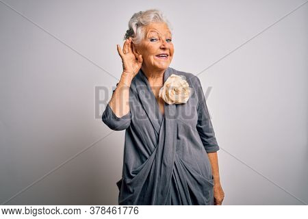 Senior beautiful grey-haired woman wearing casual dress standing over white background smiling with hand over ear listening an hearing to rumor or gossip. Deafness concept.