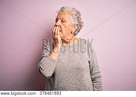 Senior beautiful woman wearing casual t-shirt standing over isolated pink background bored yawning tired covering mouth with hand. Restless and sleepiness.