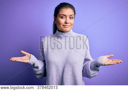 Young beautiful woman with blue eyes wearing casual turtleneck sweater over pink background clueless and confused expression with arms and hands raised. Doubt concept.