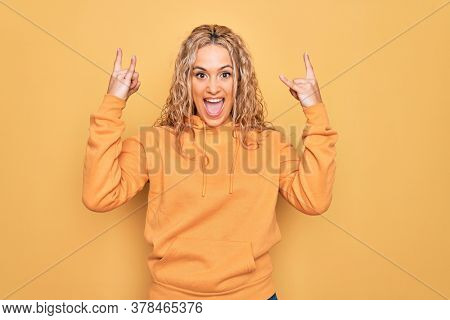 Young beautiful blonde sporty woman wearing casual sweatshirt over yellow background shouting with crazy expression doing rock symbol with hands up. Music star. Heavy music concept.