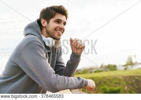 Image of joyful athletic sportsman with headphones smiling while leaning on railing outdoors