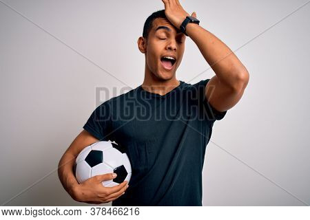 Handsome african american man playing footbal holding soccer ball over white background surprised with hand on head for mistake, remember error. Forgot, bad memory concept.