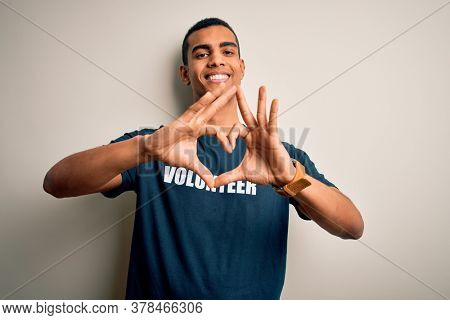 Young handsome african american man volunteering wearing t-shirt with volunteer message smiling in love doing heart symbol shape with hands. Romantic concept.