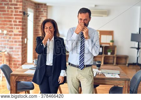 Two middle age business workers standing working together in a meeting at the office smelling something stinky and disgusting, intolerable smell, holding breath with fingers on nose. Bad smells.