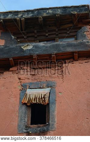 Fabric Flutters Along The Top Of An Open Window In An Old Building. The Wall Has Cracks And Is Terra
