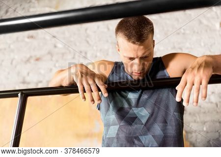 fitness, sport, training and lifestyle concept - tired young man exercising on parallel bars in gym