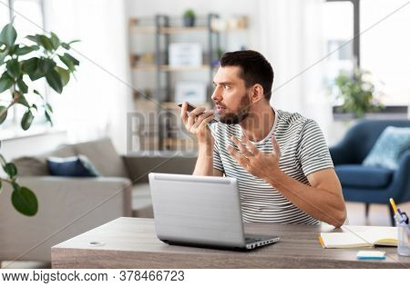 technology, remote job and people concept - angry man with laptop computer calling on smartphone or using voice command recorder at home office