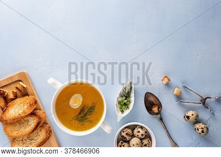 Chicken Bouillon With Dill And Quail Egg In Bowl, Baguette Toasts And Croutons On Cutting Board, Spo