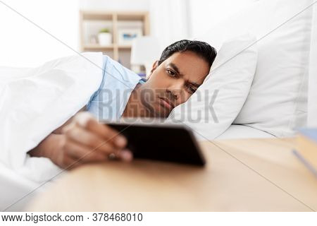 people, bedtime and rest concept - sleepy indian man with smartphone lying in bed at home