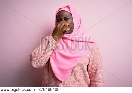 Young african american plus size woman wearing muslim hijab over isolated pink background smelling something stinky and disgusting, intolerable smell, holding breath with fingers on nose. Bad smell