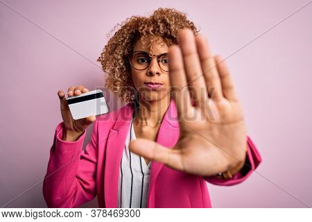 Young african american business woman holding id card identification over pink background with open hand doing stop sign with serious and confident expression, defense gesture