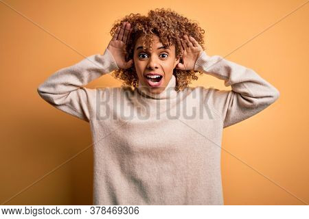 Young beautiful african american woman wearing turtleneck sweater over yellow background Smiling cheerful playing peek a boo with hands showing face. Surprised and exited