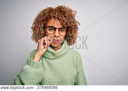 Young beautiful african american woman wearing turtleneck sweater and glasses mouth and lips shut as zip with fingers. Secret and silent, taboo talking