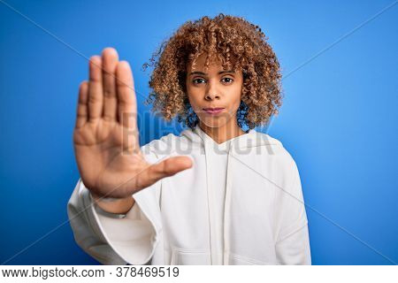 Beautiful african american sporty woman wearing casual sweatshirt over blue background doing stop sing with palm of the hand. Warning expression with negative and serious gesture on the face.