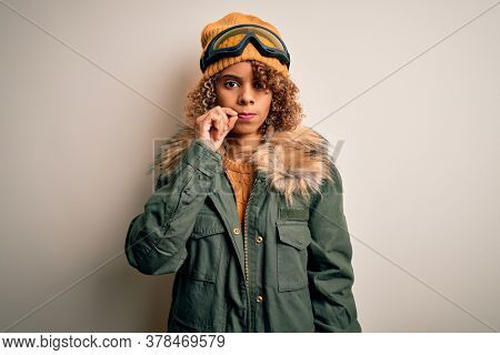 Young african american skier woman with curly hair wearing snow sportswear and ski goggles mouth and lips shut as zip with fingers. Secret and silent, taboo talking