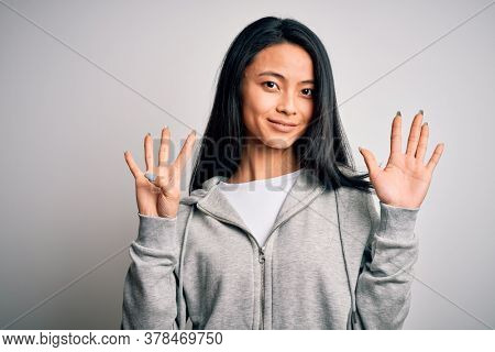 Young beautiful chinese sporty woman wearing sweatshirt over isolated white background showing and pointing up with fingers number nine while smiling confident and happy.