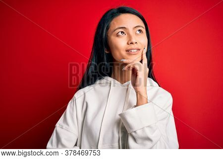 Young beautiful chinese sporty woman wearing sweatshirt over isolated red background with hand on chin thinking about question, pensive expression. Smiling with thoughtful face. Doubt concept.