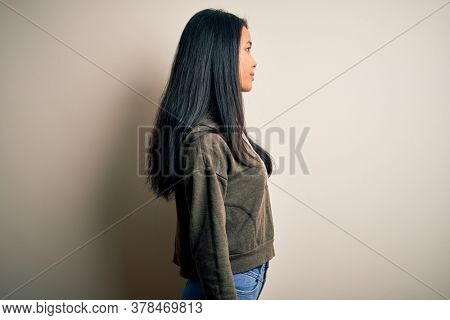 Young beautiful chinese sporty woman wearing sweatshirt over isolated white background looking to side, relax profile pose with natural face with confident smile.