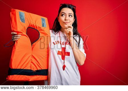 Young lifeguard woman holding rescue lifejacket over red background serious face thinking about question, very confused idea