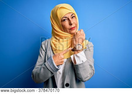 Middle age brunette business woman wearing muslim traditional hijab over blue background In hurry pointing to watch time, impatience, looking at the camera with relaxed expression