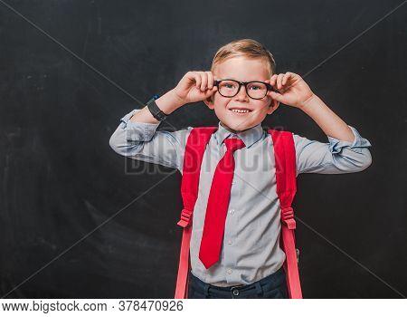 Little Kid Boy In Glasses And School Uniform Is Looking In Camera Against Chalk Blackboard. Back To
