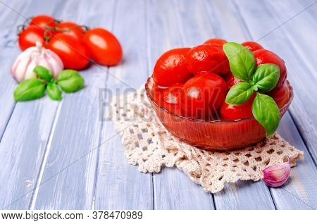 Canned Tomatoes In Their Own Juice With Basil Leaves. Selective Focus.