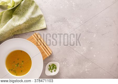 Chicken Bouillon With Green Onion In Large White Plate On Bamboo Board And With Green Linen Napkin.