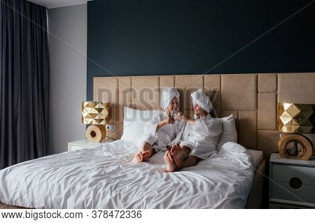 Young Couple Of Man And Woman In White Bath Robes And Towels On Their Heads Are Lying In Bed With Gl