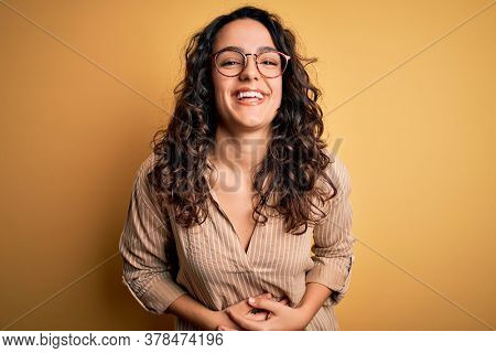 Beautiful woman with curly hair wearing striped shirt and glasses over yellow background smiling and laughing hard out loud because funny crazy joke with hands on body.