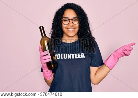 African american curly woman wearing volunteer t-shirt doing volunteering recycling glass bottle very happy pointing with hand and finger to the side