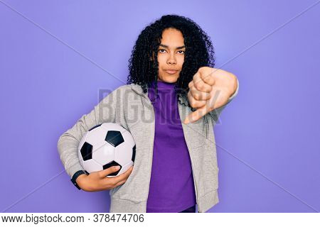 African american curly player woman playing soccer holding football bal over purple background with angry face, negative sign showing dislike with thumbs down, rejection concept