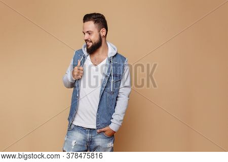 Stylish Young Cheerful Guy With A Beautiful Beard In A Denim Jacket And White T-shirt On A Plain Cre