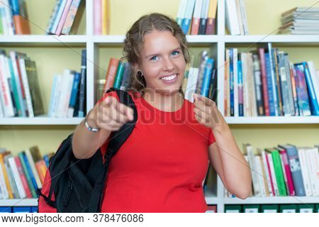 Happy German Female Student At Library Of University Looking At Camera