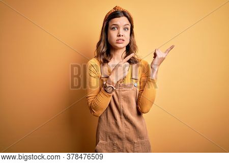 Young beautiful blonde girl wearing overall standing over yellow isolated background Pointing aside worried and nervous with both hands, concerned and surprised expression