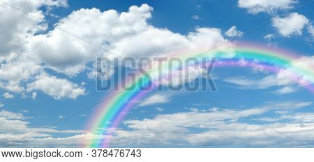 Sunny Summer Blue Sky Panoramic Rainbow - Big Fluffy Clouds With A Giant Arcing Rainbow Against A Be