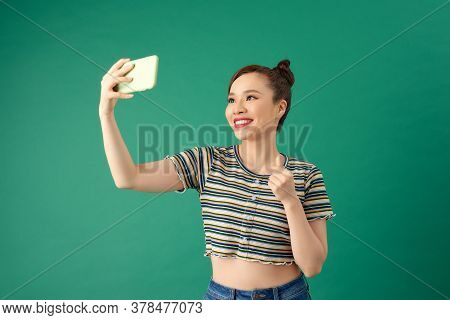 Portrait Of Young Asian Female Making Selfie Photo On Smartphone With Postitive Expression Over Gree