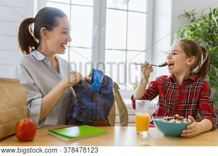 Healthy food at home. Happy family in the kitchen. Mother and child daughter are having breakfast before school.