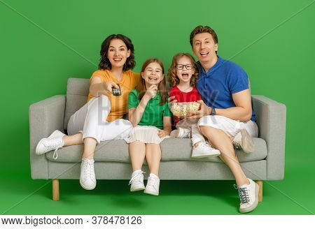 Happy loving family on bright colour background. Father, mother and daughters girls watching TV, movies with popcorn. Dad, mom and lovely children are having fun staying at home.