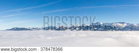 Fantastic Panoramic View Of Snow Mountain Range Stick Out Of Inversion Fog Layer. Great Panorama Wit