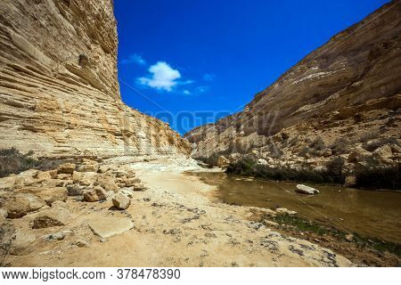 The canyon  is the most beautiful in the Negev desert. The sky is reflected in the water. The walls of the gorge are corroded by caves. The ravine Ein Avdat is formed by the Qing River.